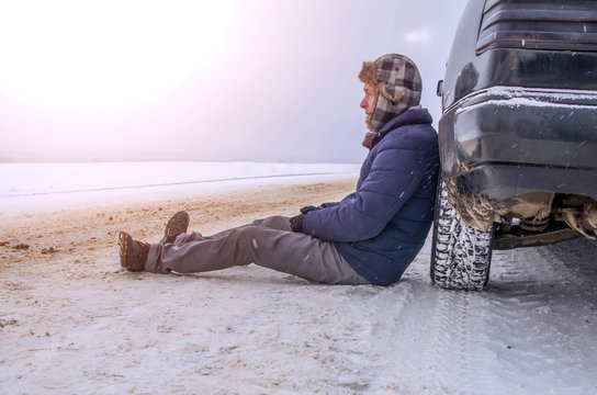 Angry young man waiting for help, sitting near the broken car on the side of the road in the winter in the woods