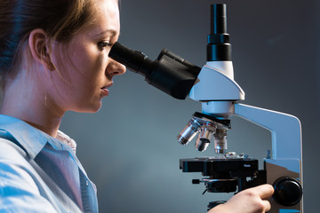 beautiful science student looking into a microscope in a laboratory