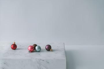 Christmas decoration balls on marble. Minimal style background.