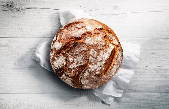 Rustikales Brot auf weißem Tuch mit weißem Holzuntergrund