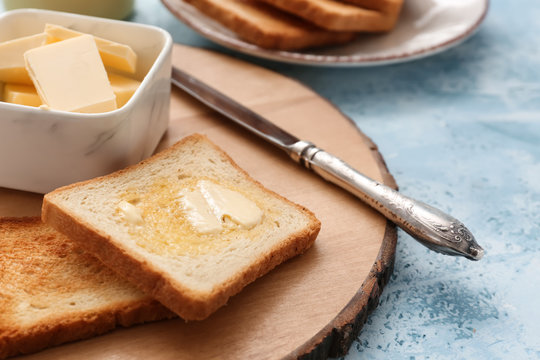Tasty toasted bread with butter on wooden board