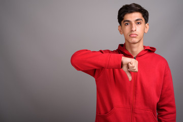 Young handsome Persian teenage boy giving thumb down