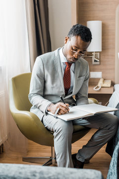 handsome african american businessman in grey suit writing in journal in hotel room