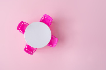 Pink chairs with white table in pastel pink room. Top view. Minimal concept.