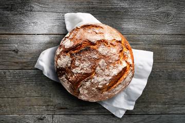 Rustikales Brot auf weißem Tuch mit dunklem Holzuntergrund