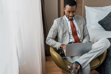 handsome smiling african american businessman working on laptop in hotel room