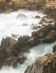 Sea waving near stony cliffs