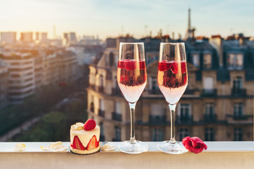 Fototapeta Paris luxury lifestyle. Pink champagne in two glasses, traditional french cake with strawberries on a balcony on the sunset obraz