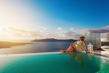 Young woman enjoying relaxation at infinity swimming pool on vacation at Santorini.