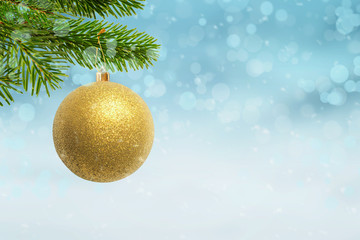 Christmas golden color ball hung on the Christmas tree. Free space beside for Christmas greeting text.