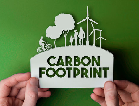 Carbon footprint - green environmental paper background with wind turbines, trees and people