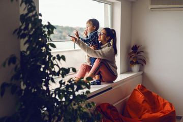 Mother sitting on the widow and holding her son. They looking through window. Mother pointing at view.