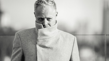Black and white photo of man in coat for walk