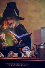 Photo of witch reading spell pumpkin in hand