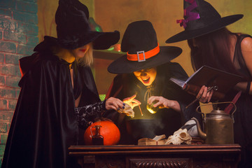 Photo of three witches in hats with book of potions making potions in cauldron