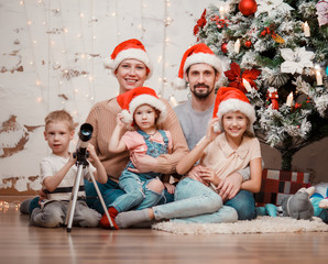 Picture of parents, two daughters in caps of Santa and son with telescope