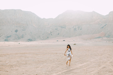 Young indian woman in white long dress walking in the desert with the mountains on background