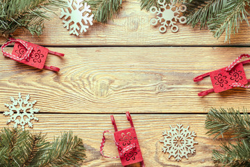 Image on top of wooden surface with branches of spruce, New Year's toys, snowflakes.