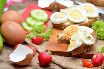 Wholegrain bread with butter, hard-boiled eggs, fresh radishes, tomatoes, salad and cucumbers in background