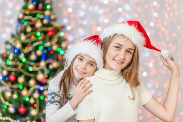 Portrait of mother and daughter in red Christmas hats near a Christmas tree