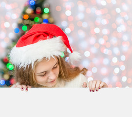 Happy girl in red christmas hat above empty white banner looking down. Space for text