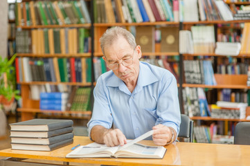 senior man reading a book in the library