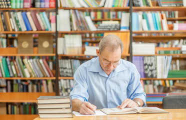 senior man reading a book in the library. Empty space for text