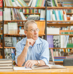 Pensive old man in the library looking away. Empty space for text