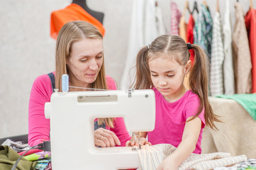 Happy mother teaches a little girl to sew on a sewing machine