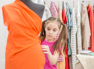 Little girl measuring  fabric on dummy in workshop