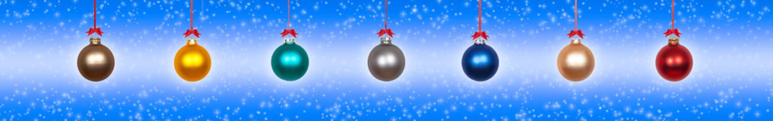 Bunte hängende Weihnachtskugeln vor blauem Hintergrund