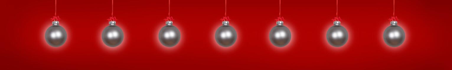 Silberne Weihnachtskugeln vor rotem Hintergrund