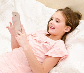 Cute smiling little girl child with her mobile phone smartphone lying on the bed