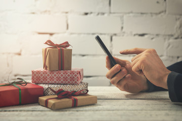 man using smartphone to buy gifts online at internet store