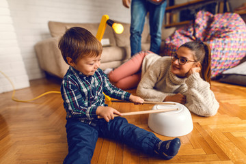 Cute little kid sitting on the floor and pretending to play drums. Mother watching him and smiling. Home interior.