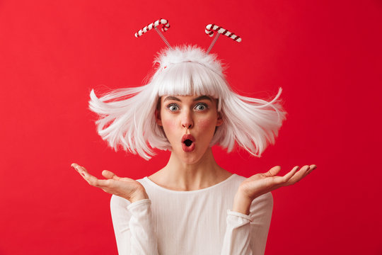 Excited young shocked woman dressed in carnival christmas costume posing isolated over red wall background.