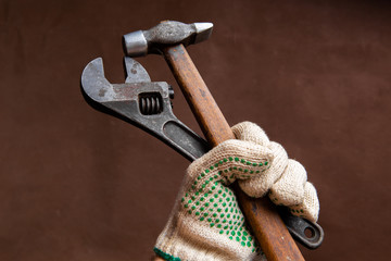 armful of rusty old vintage retro wrench spanner and hammer in hand wearing protective glove, on brown background, closeup