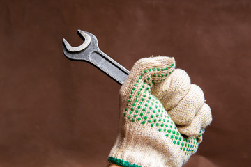 armful of rusty old vintage retro wrench spanner in hand wearing protective glove, on brown background, closeup