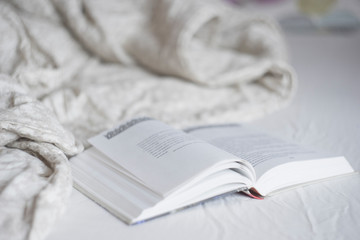 Book reading in the bed, calm and cozy morning mood photo, grey and beige blanket and sheets. Home lifestyle