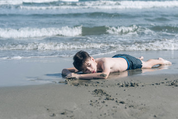 Happy teen boy sleeping on the sand оn the beach