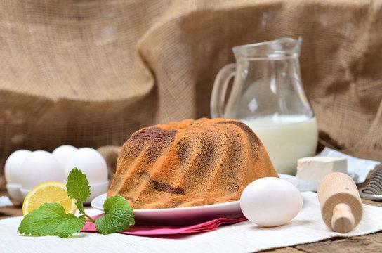 Homemade lemon bundt cake with lemon, melissa, milk, eggs and tea