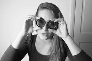 Young woman looking through camera lens and smile. Photography tools and equipment. Black and white photo.