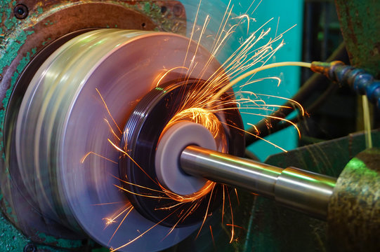Production of parts in the metalworking industry, finishing on an internal steel surface grinding machine with flying sparks.