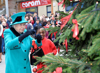 Britain's Queen Elizabeth and Shylah Gordon, aged 8, attach a bauble to a Christmas tree during a visit to children's charity Coram in London