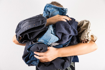 Woman holding huge pile of dirty clothes