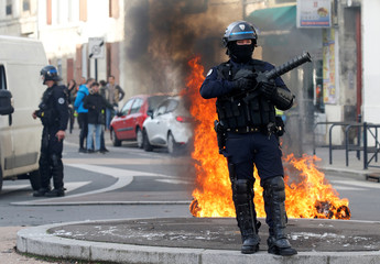 A French policeman stands next to a burning trash container as youth and students protest against reform plan in the streets of Bordeaux
