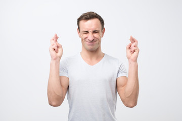Hopeful young italian male crosses fingers before having job interview, worries much