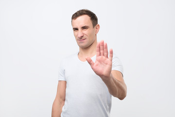 Young italian man shows stop timeout or refusal sign with hand