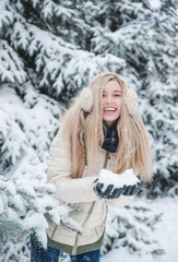 Beautiful smiling woman has a fun with snow outdoor. Lifestyle. Winter holidays.
