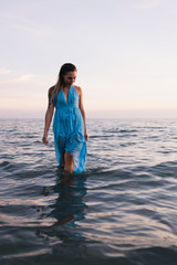Young woman wearing blue dress walking in water at seashore  by sunset